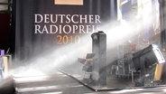 """Vorhang mit der Aufschrift """"Deutscher Radiopreis 2010"""" und Scheinwerfer © Bild: NDR/Karsten Schmeer Foto: Karsten Schmeer"""