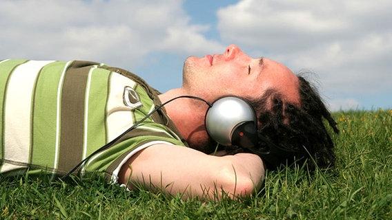 Ein junger Mann mit Kopfhörern liegt im Gras und hört Musik. © Edyta Pawlowska - Fotolia