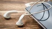 Nahaufnahme von Kopfhörern an einem Smartphone © colourbox Foto: showcake