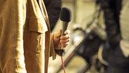 Eine Person mit Mantel hält ein Mikrofon in der Hand. © fotolia Fotograf: wellphoto